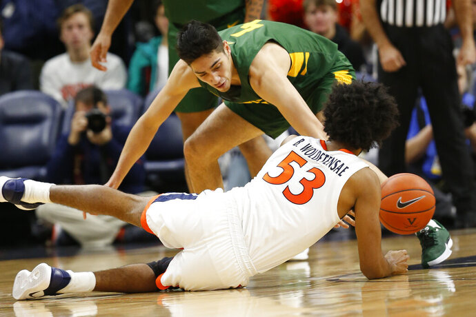 Virginia guard Tomas Woldetensae (53) goes after a loose ball along with Vermont guard Robin Duncan (4) during the first half of an NCAA college basketball game Tuesday, Nov. 19, 2019, in Charlottesville, Va. (AP Photo/Steve Helber)
