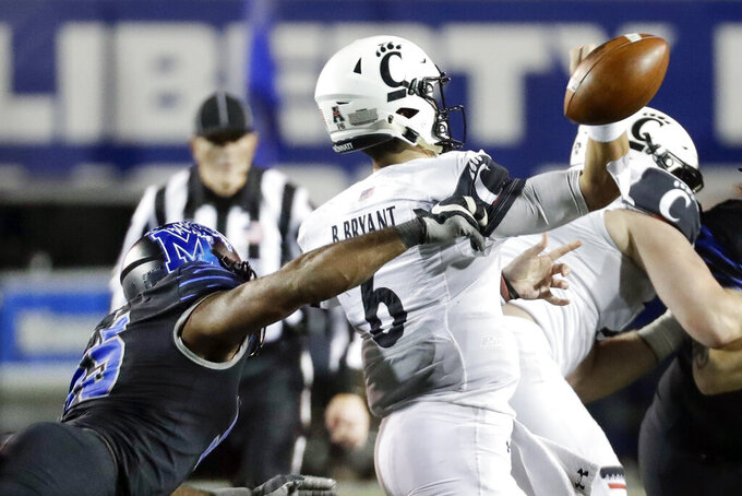 Memphis defensive end Bryce Huff, left, hits the arm of Cincinnati quarterback Ben Bryant (6) as Bryant throws in the second half of an NCAA college football game Friday, Nov. 29, 2019, in Memphis, Tenn. The play resulted in a fumble and Cincinnati recovered the ball. (AP Photo/Mark Humphrey)