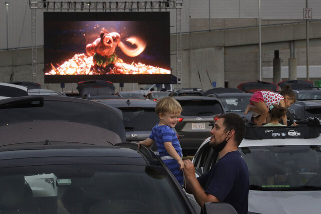 Kevin Rokos, right, and his one-year-old son Merritt, both of Boston, attend a drive-in movie screening of the film