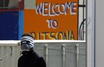 A young migrant covering his face to protect from the new coronavirus stands at the entrance of the Ritsona refugee camp about 80 kilometers (50 miles) north of Athens on Thursday, April 2, 2020. Greek authorities have placed the refugee camp under 14 days quarantine after 20 of its residents tested positive for the COVID-19. During this period nobody would be allowed in or out of the facility. (AP Photo/Thanassis Stavrakis)