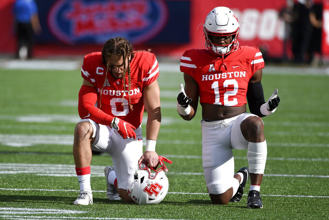 Houston linebacker Grant Stuard (0) and linebacker Ke'Andre Street pause before an NCAA college football game against South Florida, Saturday, Nov. 14, 2020, in Houston. (AP Photo/Eric Christian Smith)