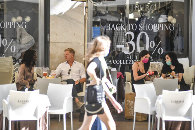 People sit at a cafe in Milan, Italy, Monday, May 18, 2020. On Monday, Italians enjoyed a first day of regained freedoms, including being able to sit down at a cafe or restaurant, shop in all retail stores or attend church services such as Mass. (Marco Alpozzi/LaPresse via AP)