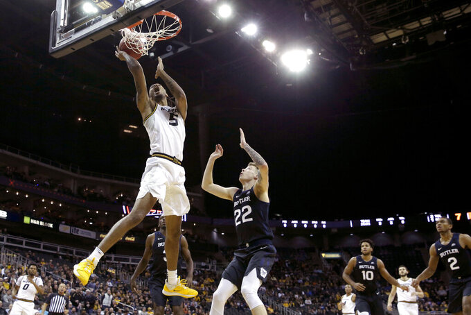 Missouri forward Mitchell Smith (5) shoots under pressure from -Butler forward Sean McDermott (22) during the first half of an NCAA college basketball game Monday, Nov. 25, 2019, in Kansas City, Mo. (AP Photo/Charlie Riedel)