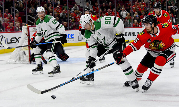 Dallas Stars center Jason Spezza (90) moves the puck against Chicago Blackhawks defenseman Erik Gustafsson (56) during the first period of an NHL hockey game Friday, April 5, 2019, in Chicago. (AP Photo/Matt Marton)