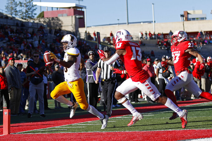 Wyoming wide receiver Austin Conway, left, scores a touchdown ahead of New Mexico cornerback Jalin Burrell (13) and safety Marcus Hayes (23) during the second half of an NCAA college football game in Albuquerque, N.M., Saturday, Nov. 24, 2018. Wyoming won 31-3. (AP Photo/Andres Leighton)