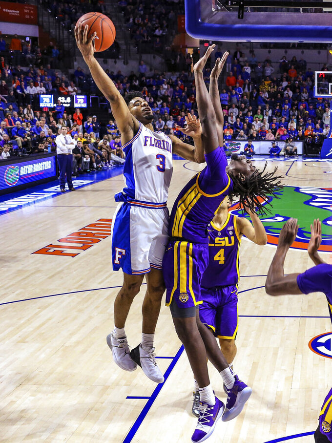 Florida guard Jalen Hudson (3) fends off LSU forward Naz Reid (0) on a shot during overtime of an NCAA college basketball game in Gainesville, Fla., Wednesday, March 6, 2019. (AP Photo/Gary McCullough)