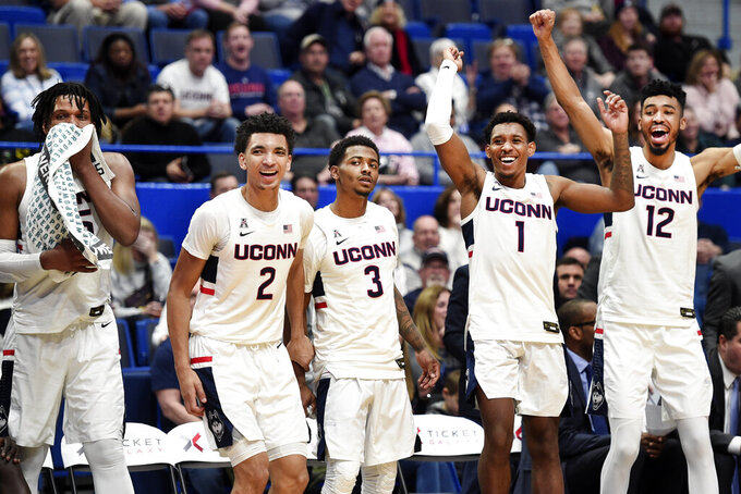 Connecticut's Josh Carlton (25), James Bouknight (2) , Alterique Gilbert (3), Christian Vital (1), and Tyler Polley (12) cheer for a bench player in the closing seconds of their game against the New Jersey Institute of Technology during an NCAA college basketball game Sunday, Dec. 29, 2019, in Hartford, Conn. (AP Photo/Stephen Dunn)