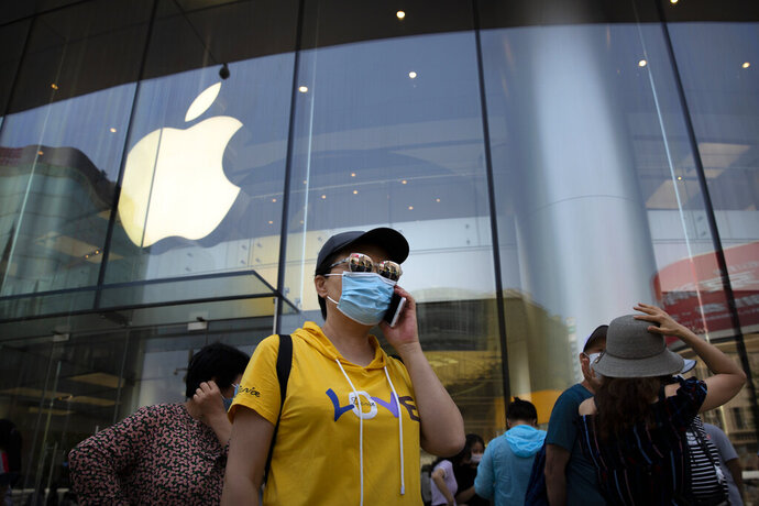 People wearing face masks to protect against the new coronavirus stand outside of an Apple store in Beijing, Saturday, June 6, 2020. China's capital is lowering its emergency response level to the second-lowest starting Saturday for the coronavirus pandemic. That will lift most restrictions on people traveling to Beijing from Wuhan and surrounding Hubei province, where the virus first appeared late last year. (AP Photo/Mark Schiefelbein)