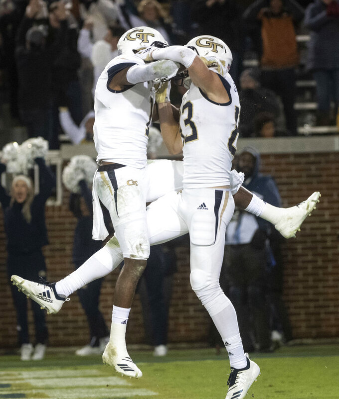Georgia Tech running back Qua Searcy, left, celebrates a touchdown catch in the end zone by wide receiver Brad Stewart, right, during the second half of an NCAA college football game against Miami on Saturday, Nov. 10, 2018, in Atlanta. Georgia Tech won 27-21. (AP Photo/John Amis)