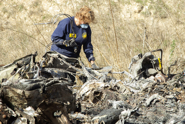 FILE - In this Jan. 27, 2020, file photo, released by the National Transportation Safety Board, NTSB investigator Carol Hogan examines wreckage as part of the NTSB's investigation of a helicopter crash near Calabasas, Calif., that killed former NBA basketball player Kobe Bryant, his 13-year-old daughter, Gianna, and seven others. Federal safety investigators bypassed aviation regulators on Tuesday, June 2, 2020, and urged leading helicopter manufacturers to install so-called black boxes that would help determine the cause of crashes such as the one that killed former NBA star Kobe Bryant.(James Anderson/National Transportation Safety Board via AP, File)