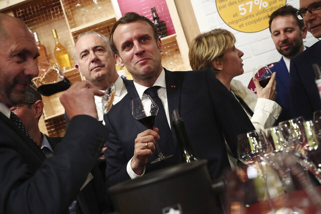 French President Emmanuel Macron drinks wine during a visit to the International Agriculture Fair (Salon de l'Agriculture) at the Porte de Versailles exhibition center in Paris, Saturday, Feb. 22, 2020. (Christophe Petit Tesson/Pool via AP)