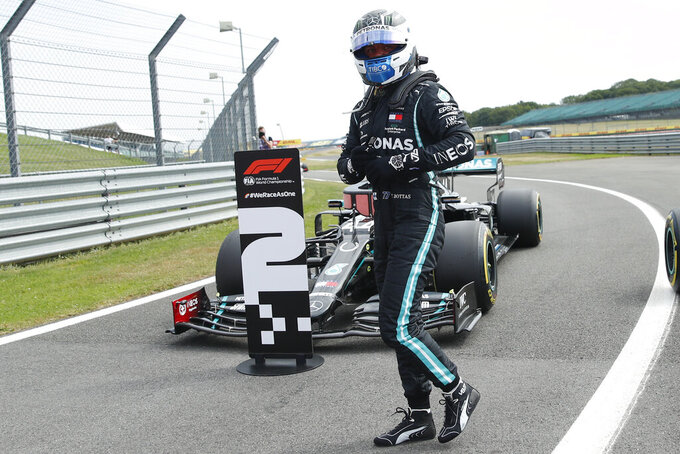 Mercedes driver Valtteri Bottas of Finland celebrates setting the fastest time ahead of Lewis Hamilton of Britain, background, during qualifying for the 70th Anniversary Formula One Grand Prix at the Silverstone circuit, Silverstone, England, Saturday, Aug. 8, 2020. (Andrew Boyers/Pool Photo via AP)