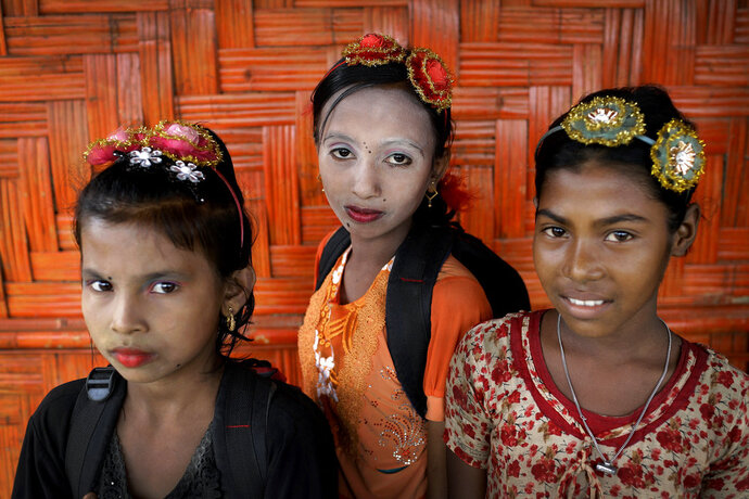 In this June 27, 2018, photo, from left, Ranjeda, 9, Rumana, 10, and Zesmin, 10 pose for a portrait in front of their classroom in Chakmarkul refugee camp, Bangladesh. Amid the misery and mud of Bangladesh's refugee camps, Rohingya girls have found small moments of joy by adorning themselves with flowery headbands and elaborately-drawn makeup. (AP Photo/Wong Maye-E)