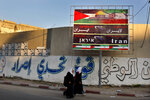 FILE - In this Nov. 28, 2012 file photo, Palestinian school girls pass a billboard covered by Palestinian and Iranian flags with Arabic that reads,