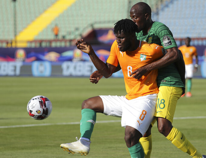 FILE - In this June 24, 2019, file photo, Ivory Coast's Franck Kessie receives the ball in front of South Africa's Sandile Hlanti during an African Cup of Nations group D soccer match in Cairo. The only time the Ivory Coast men have competed at the Olympics was in 2008 when they faced Lionel Messi's Argentina before going out in the quarterfinals. They will be hoping to secure the release from Manchester United of Amad Diallo and Kessie from AC Milan. (AP Photo/Hassan Ammar, File)