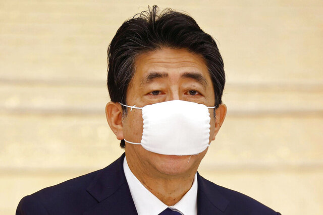 Japan's Prime Minister Shinzo Abe speaks during a meeting of government and ruling party officials at his office in Tokyo Wednesday, May 27, 2020. Japan's Cabinet has approved a proposed 32 trillion-yen ($296 billion) supplementary budget to help fund measures to cushion the blow to the economy from the coronavirus pandemic. (Kyodo News via AP)