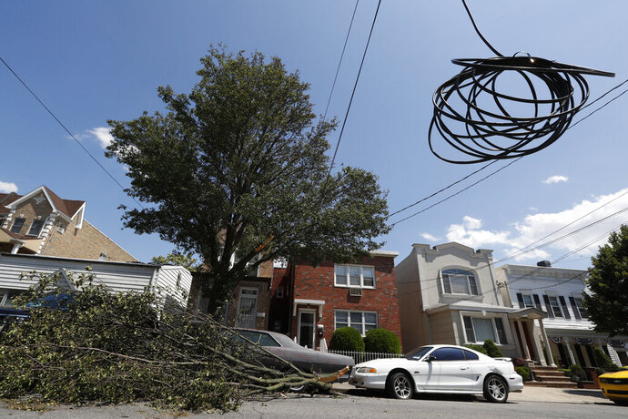 A coiled power line hangs along with electrical wires in a residential neighborhood of Middle Village, Queens, where some homes and businesses lost power in the wake of Tropical Storm Isaias, Wednesday, Aug. 5, 2020, in New York. At the peak of the storm over 130,000 customers had lost power, according the New York Mayor Bill DeBlasio. (AP Photo/Kathy Willens)