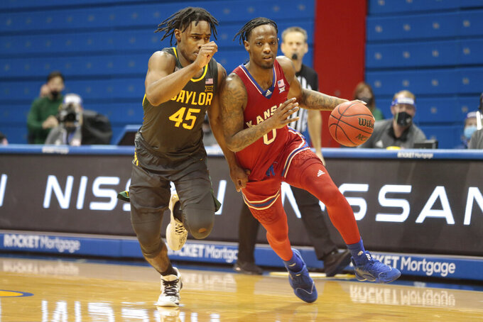 Kansas guard Marcus Garrett, front right, avoids Baylor guard Davion Mitchell (45) in the second half of an NCAA college basketball game in Lawrence, Kan., Saturday, Feb. 27, 2021. (Evert Nelson/The Topeka Capital-Journal via AP)