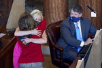 Nebraska state Sen. Suzanne Geist of Lincoln, left, is hugged by Sen. Julie Slama of Peru as Sen. Mike Hilgers of Lincoln watches, following the passage of LB814, Geist's bill to prohibit the dilation and evacuation procedure during an abortion, in Lincoln, Neb., Thursday, Aug. 13, 2020, on the last day of a legislative session marked by major disruptions from the coronavirus and political feuds that often turned personal. (AP Photo/Nati Harnik)