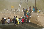 A dust storm moves across the area as Haitian migrants use a dam to cross into the United States from Mexico, Saturday, Sept. 18, 2021, in Del Rio, Texas. U.S. officials said that within the next three days, they plan to ramp up expulsion flights for some of the thousands of Haitian migrants who have gathered in the Texas city from across the border in Mexico. (AP Photo/Eric Gay)