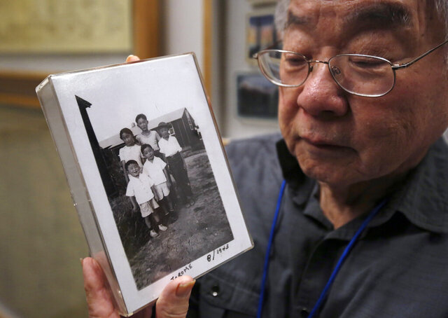 In this photo taken Tuesday, Feb. 11, 2020, Les Ouchida holds a 1943 photo of himself, front row, center, and his siblings taken at the internment camp his family was moved to, as he poses at the permanent exhibit titled