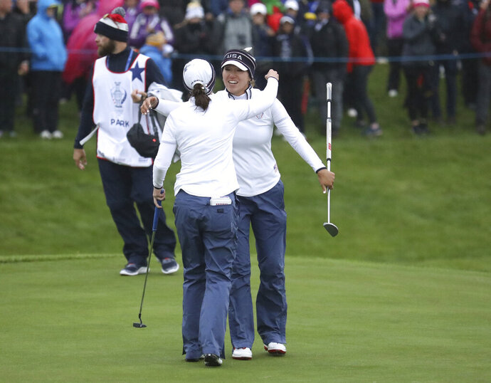 Annie Park, left, and Brittany Altomare of the US celebrate on the 18th green after finishing 1 up against Europe during the Fourballs match in the Solheim cup at Gleneagles, Auchterarder, Scotland, Saturday, Sept. 14, 2019. (AP Photo/Peter Morrison)