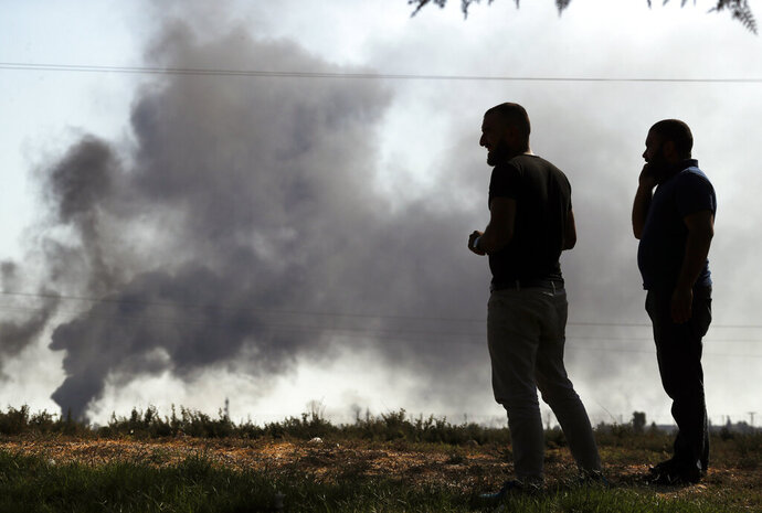 People in Akcakale ,Sanliurfa province, southeastern Turkey, at the border with Syria, watch smoke billowing from targets inside Syria, during bombardment by Turkish forces, Thursday, Oct. 10, 2019. Turkey's foreign minister says Turkish troops intend to move some 30 kilometers (19 miles) deep into northern Syria and that its operation will last until all