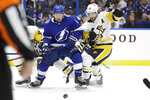 Tampa Bay Lightning center Tyler Johnson (9) and Pittsburgh Penguins defenseman Kris Letang (58) chase the puck during the second period of an NHL hockey game Thursday, Feb. 6, 2020, in Tampa, Fla. (AP Photo/Chris O'Meara)