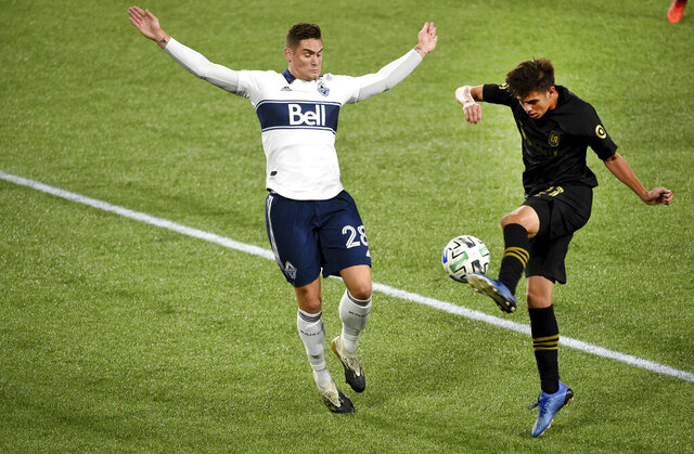 Los Angeles FC forward Christian Torres, right, kicks the ball as Vancouver Whitecaps defender Jake Nerwinski, left, defends during the first half of an MLS soccer match in Portland, Ore., Wednesday, Oct. 14, 2020. (AP Photo/St eve Dykes)