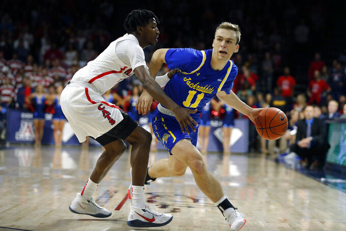 South Dakota State guard Noah Freidel (11) drives against Arizona guard Dylan Smith in the first half during an NCAA college basketball game, Thursday, Nov. 21, 2019, in Tucson, Ariz. (AP Photo/Rick Scuteri)