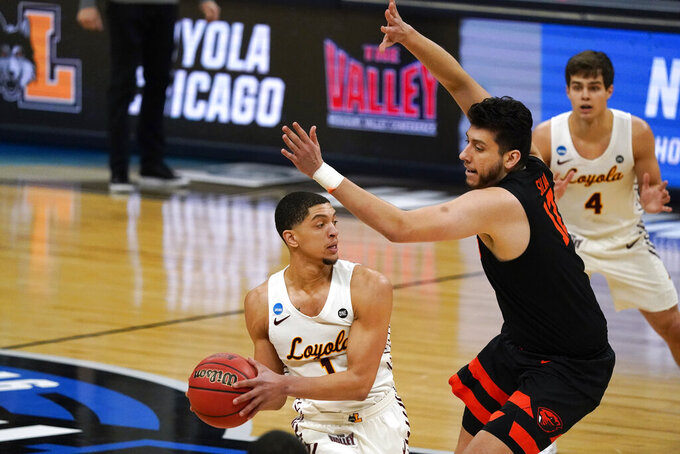 Loyola Chicago guard Lucas Williamson (1) passes around Oregon State center Roman Silva (12) during the first half of a Sweet 16 game in the NCAA men's college basketball tournament at Bankers Life Fieldhouse, Saturday, March 27, 2021, in Indianapolis. (AP Photo/Jeff Roberson)