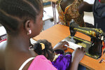 In this photo taken on Thursday Aug. 22, 2019, a former child soldier sits with her daughter on her lap, partaking in a skills training program learning to sew in Yambio, South Sudan. An estimated 19,000 child soldiers are in South Sudan, one of the highest rates in the world, according to the United Nations. As the country emerges from civil war, some worry the fighting could re-ignite if former child soldiers aren't properly reintegrated into society.  (AP Photo/Sam Mednick)