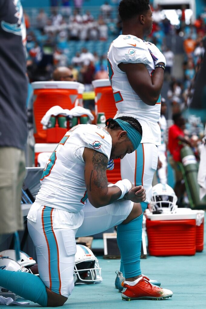 Miami Dolphins wide receiver Albert Wilson (15) kneels during the national anthem, before, an NFL football game against the Washington Redskins, Sunday, Oct. 13, 2019, in Miami Gardens, Fla. (AP Photo/Brynn Anderson)