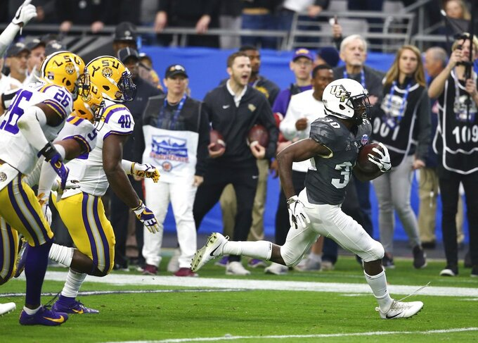 UCF running back Greg McCrae (30) runs for a touchdown beating LSU safety John Battle (26), safety Grant Delpit (9), and linebacker Devin White (40) during the first half of the Fiesta Bowl NCAA college football game Tuesday, Jan. 1, 2019, in Glendale, Ariz. (AP Photo/Ross D. Franklin)
