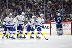 Tampa Bay Lightning's Carter Verhaeghe (23) and teammates celebrate his goal against Winnipeg Jets goaltender Connor Hellebuyck (37) during second-period NHL hockey game action in Winnipeg, Manitoba, Friday, Jan. 17, 2020. (John Woods/The Canadian Press via AP)