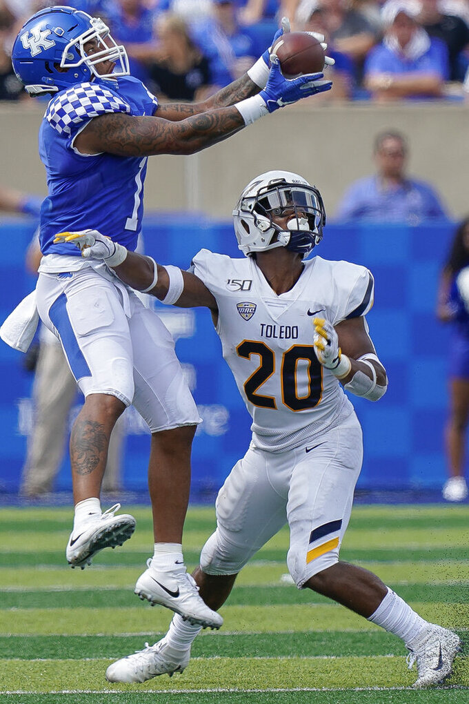 Kentucky wide receiver Lynn Bowden Jr. (1) catches a pass over the head of Toledo safety Saeed Holt (20) during the second half of the NCAA college football game, Saturday, Aug. 31, 2019, in Lexington, Ky. (AP Photo/Bryan Woolston)