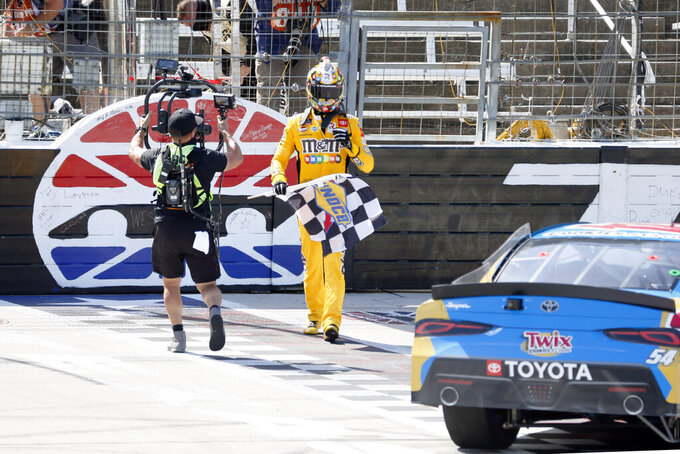 ADDS THAT BUSCH WAS DISQUALIFIED - Kyle Busch walks back to his car with the checkered flag after winning the NASCAR Xfinity auto race at Texas Motor Speedway in Fort Worth, Texas, Saturday, July 18, 2020.  Kyle Busch celebrated a 10th NASCAR Xfinity Series victory at Texas, and then had it taken away. Busch failed postrace tech inspection Saturday after finishing ahead of Austin Cindric, who was declared the winner for the third victory in a row after winning both Xfinity races at Kentucky.(AP Photo/Ray Carlin)
