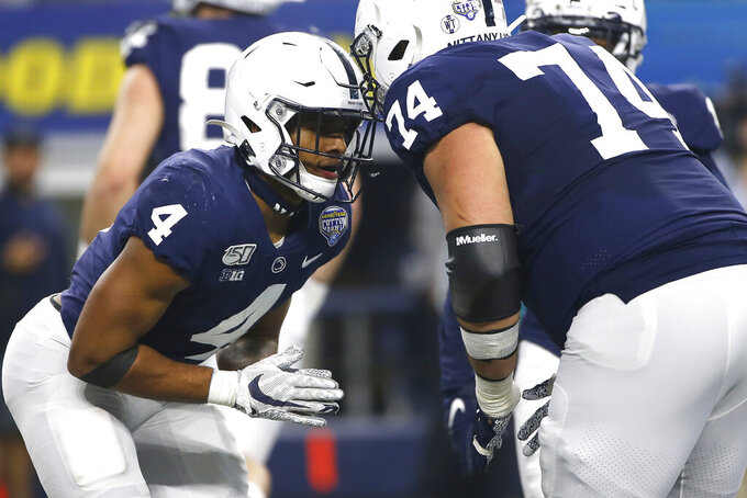 Penn State running back Journey Brown (4) and teammate offensive lineman Steven Gonzalez (74) celebrate after Brown scored a touchdown against Memphis in the first half of the NCAA Cotton Bowl college football game, Saturday, Dec. 28, 2019, in Arlington, Texas. (AP Photo/Ron Jenkins)