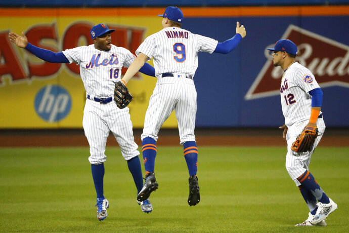 New York Mets left fielder Rajai Davis (18) celebrates with center fielder Brandon Nimmo (9) as right fielder Juan Lagares (12) heads toward the dugout after the Mets' 9-0 win over Arizona Diamondbacks in a baseball game Wednesday, Sept. 11, 2019, in New York. (AP Photo/Kathy Willens)