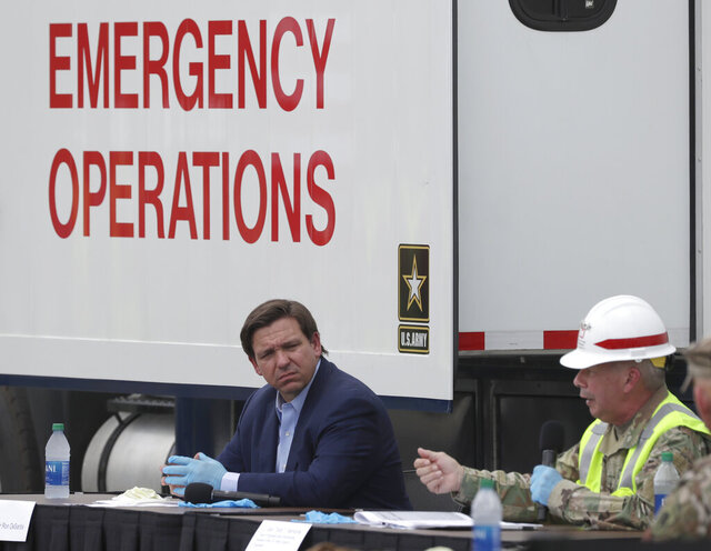 Florida Gov. Ron DeSantis, center, listens as Chief of Engineers and Commanding General of the U.S. Army Corps of Engineers Lt. Gen. Todd T. Semonite, right, speaks during a news conference in front of a U.S. Army Corps of Engineers mobile command center at the Miami Beach Convention Center, Wednesday, April 8, 2020, in Miami Beach, Fla. The Corps of Engineers will transform the newly renovated facility into a hospital by April 27, news outlets reported Tuesday. (AP Photo/Wilfredo Lee)