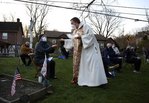 The Rev. Noah Evans of St. Paul's Episcopal Church gives communion to his parishioners, who are scattered throughout the burial grounds of Old St. Luke's Church during their Easter sunrise service on Sunday, April 4, 2021, in Carnegie, Pa. For many congregants, this was the first in-person worship service they have attended since the coronavirus surge in November. (AP Photo/Jessie Wardarski)