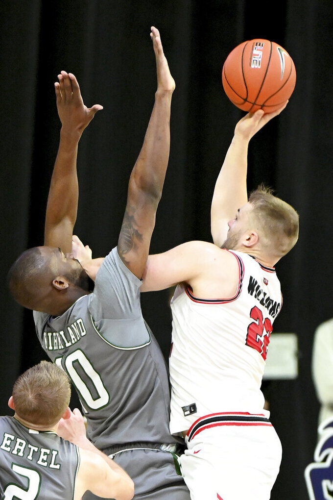 Western Kentucky forward Carson Williams (22) shoots over UAB forward Simeon Kirkland (10) in the second half of an NCAA college basketball game in the Conference USA men's tournament, in Frisco, Texas, Friday, March 12, 2021. Western Kentucky won 64-60. (AP Photo/Matt Strasen)