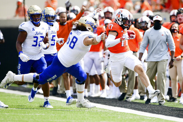 Tulsa defender Deven Lamp (58) chases Oklahoma State wide receiver Dillon Stoner (17) out of bounds in the first half of an NCAA college football game Saturday, Sept. 19, 2020, in Stillwater, Okla. (AP Photo/Brody Schmidt)