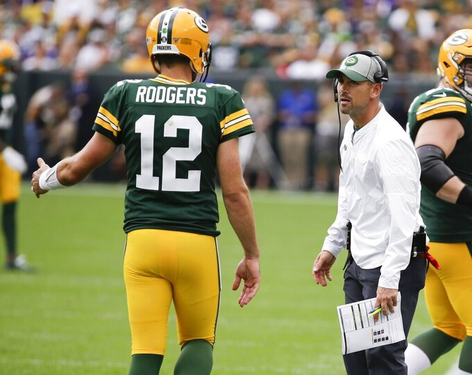 Green Bay Packers head coach Matt LaFleur talks to Aaron Rodgers during the first half of an NFL football game against the Minnesota Vikings Sunday, Sept. 15, 2019, in Green Bay, Wis. (AP Photo/Mike Roemer)