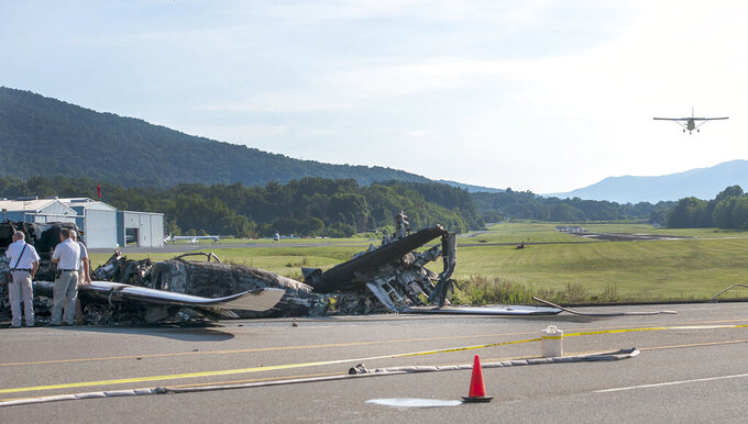 A small plane lands Friday, Aug. 16, 2019, behind the wreckage of a plane that Dale Earnhardt Jr., his wife and daughter and two pilots and a dog were on when it crash landed Thursday at the Elizabethton Municipal Airport in Elizabethton, Tenn. Earnhardt Jr. will take the weekend off from broadcasting to be with his wife and daughter after the crash near Bristol Motor Speedway. (David Crigger/Bristol Herald Courier via AP)
