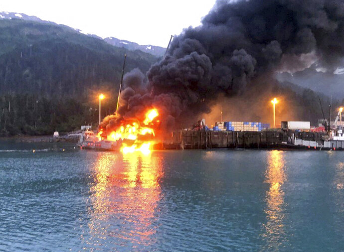 This photo provided by the U.S. Coast Guard shows the fishing boat Alaganik burning at a dock in Whittier, Alaska, in the early morning hours of Monday, July 8, 2019. The Coast Guard says a propane tank exploded around midnight Sunday on the 99-foot (30-meter) fishing vessel at a dock operated by the city of Whittier. The boat burned and sank at the dock. (U.S. Coast Guard via AP)
