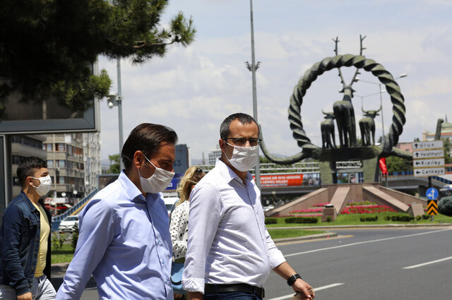 People wearing face masks to protect against the spread of coronavirus, walk in the city's historical part of Ulus, in Ankara, Turkey, Thursday, June 18, 2020. Turkish authorities have made the wearing of masks mandatory in three major cities to curb the spread of COVID-19 following an uptick in confirmed cases since the reopening of many businesses.(AP Photo/Burhan Ozbilici)