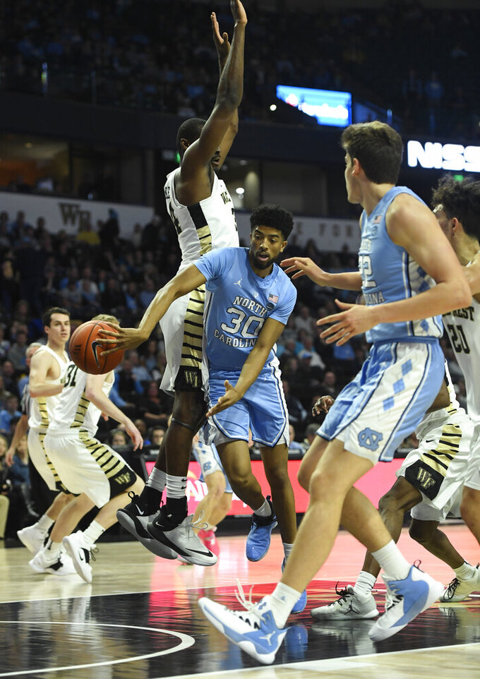 North Carolina's K.J. Smith (30) makes a pass to his teammate under the basket as Wake Forest's Sunday Okeke (34) tries to defend during the second half of an NCAA college basketball game in Winston-Salem, N.C.,  Saturday, Feb 16, 2019. (AP Photo/Woody Marshall)