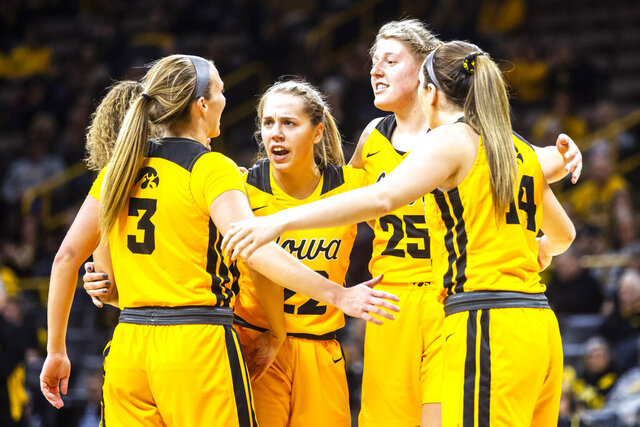 Iowa's Kathleen Doyle, third from left, and Monika Czinano (25) huddle up with teammates Iowa guard Gabbie Marshall, far left, Makenzie Meyer (3) and McKenna Warnock (14) during an NCAA college basketball game against Ohio State, Thursday, Jan. 23, 2020 in Iowa City, Iowa. (Joseph Cress/Iowa City Press-Citizen via AP)