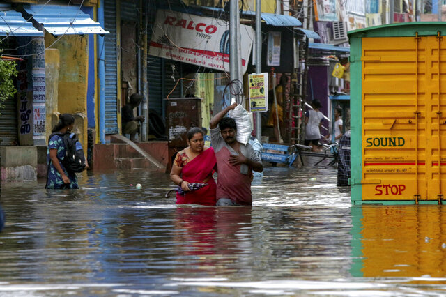 People wade through a flooded street in Chennai, India, Wednesday, Nov.25, 2020. India's southern state of Tamil Nadu is bracing for Cyclone Nivar that is expected to make landfall on Wednesday. The state authorities have issued an alert and asked people living in low-lying and flood-prone areas to move to safer places. (AP Photo/R. Parthibhan)